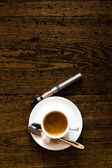 Cup of coffee and e-cigarette on a wooden counter — Stock Photo