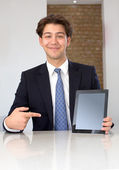 Pleased businessman pointing at a blank tablet — Stock Photo