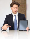 Businessman pointing to a tablet in horror — Stock Photo