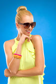 Elegance woman in sunglasses on blue background. — Stock Photo