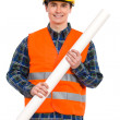 Smiling construction worker holding rolled paper plan. — Foto de Stock