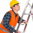 Construction worker in reflective clothing climbing a ladder. — Stock Photo #38254565