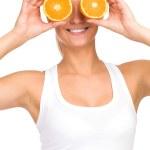 Woman holding orange over eyes — Stock Photo