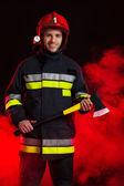 Fireman in smoke posing with axe. — Stock Photo