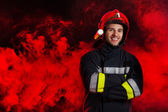 Firefighter in red helmet posing with arms crossed. — Stock Photo