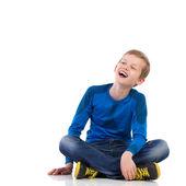 Ridendo giovane ragazzo seduto sul pavimento. — Foto Stock