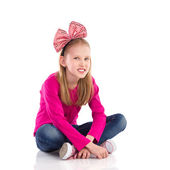 Little girl with hair bow sitting with legs crossed. — Stock Photo