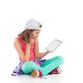 读一些东西在平板电脑上数字的女孩. — 图库照片