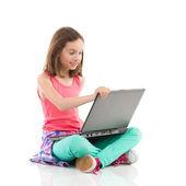 微笑的小女孩,用一台笔记本电脑 — 图库照片