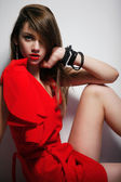 Pretty woman in red dress sitting on the floor — Stock Photo