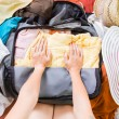 Woman trying to pack clothes in a bag — Stock Photo
