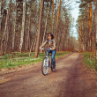 Young woman riding bicycle on a forest — Stock Photo