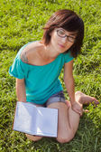 Beautiful girl with book on the meadow — Stock Photo