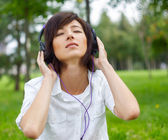 Woman listening music on the nature — Stock Photo