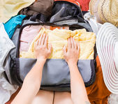 Woman trying to pack clothes in a bag — Foto de Stock