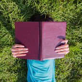 Girl with a book on meadow — Stock Photo