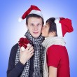 Woman kissing man with Christmas gift box — Stock Photo