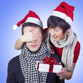 Woman surprising man with gift for New Year — Stock Photo