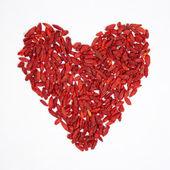Goji berries in heart shape — Stock Photo