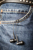Ear phones hanging out of pocket — Stock Photo