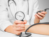Doctor measures blood pressure by sphygmomanometer — Stock Photo