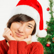 Beautiful woman in a santa hat smiles — Stock Photo