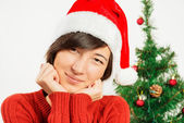 Beautiful woman in a santa hat smiles — Stockfoto