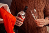 Bottle of champagne in holiday clothes — Stock Photo