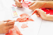 Mom and Dad help the child paint heart — Stock Photo