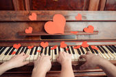 Couple is playing on piano on Valentine's Day — Stock Photo