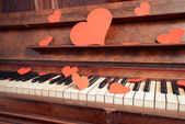 Piano with paper hearts — Stock Photo