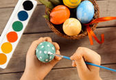 Child paints egg for Easter, focus on eggs — Stock Photo