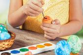 Girl paints Easter egg in orange color — Stockfoto