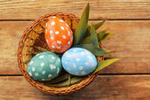 Basket with colored eggs on a wooden table — Foto de Stock