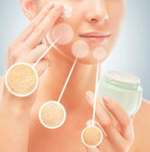 Woman applies cream on face — Stock Photo