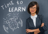 Woman stands near blackboard — Stock Photo