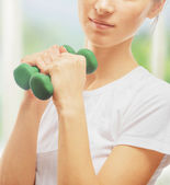 Woman is doing exercises with dumbbells — Stockfoto
