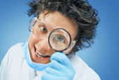 Bizarre scientist looks through a magnifying glass — Stock Photo