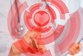 Doctor is touching shape of red heart  — Stock Photo