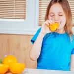 Cute girl drinks orange juice — Stock Photo
