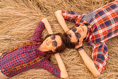 Young couple rests on dry grass — Foto Stock