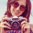 Woman holds old photo camera — Stock Photo