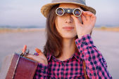 Woman looks through binoculars — Stock Photo