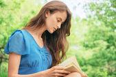 Girl reads a book outdoor — Stockfoto