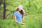 Woman reads a book in summer park — Stockfoto