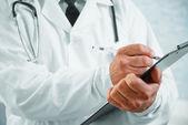 Człowiek starszy lekarz pisze dokumentacji medycznej — Zdjęcie stockowe