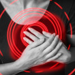 Woman is clutching her chest, heart attack, pain area of red col — Stock Photo #47860077