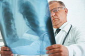 Older doctor is analyzing x-ray image — Stock Photo