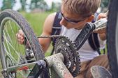 Hombre ciclista comprueba cadena — Foto de Stock