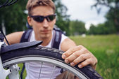 Cyclist checks wheel — Stock Photo